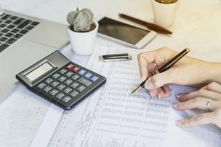 mão com caneta checando tabela em papel