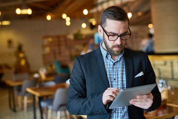 Pessoa em restaurante com tablet trabalhando