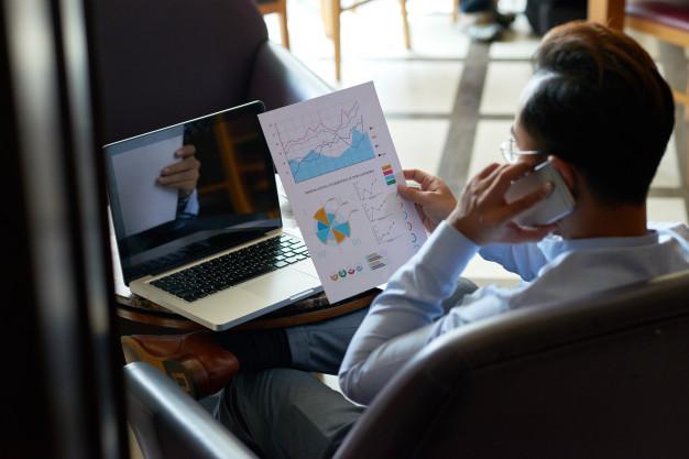 homem trabalhando em multitarefas finanças telefone notebook
